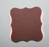 Back of pink curly tag with chocolate tag perpendicular